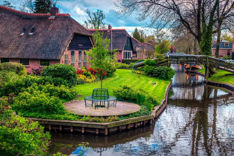 Dutch village with colorful ornamental garden and water canal, Giethoorn royalty free stock photography