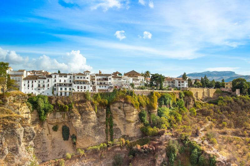 Ronda restaurants and colonial houses overlooking the scenic gorge and the Puente Nuevo bridge. Famous Ronda restaurants and colonial houses overlooking the royalty free stock photography