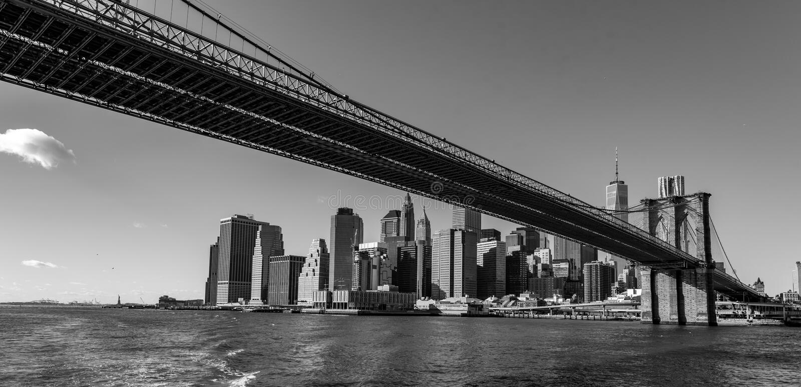 Famous Skyline of downtown New York City, Brooklin Bridge and Manhattan with skyscrapers illuminated over East River panorama. New royalty free stock photography