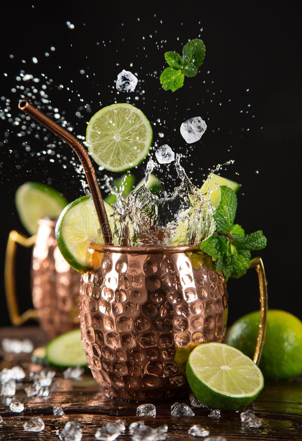 Famous splashing Moscow mule alcoholic cocktail in copper mugs. Famous splashing Moscow mule alcoholic cocktail in copper mugs, freeze motion effect royalty free stock photography
