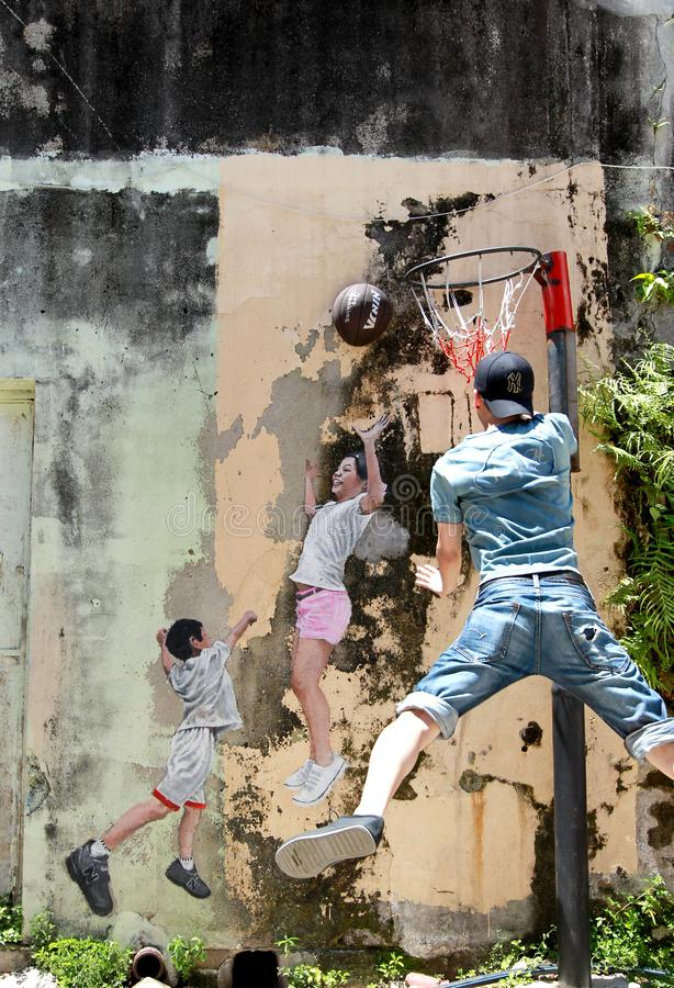Famous street art mural in George Town. `Children playing basketball` street art mural in George Town, Penang, Malaysia stock photography