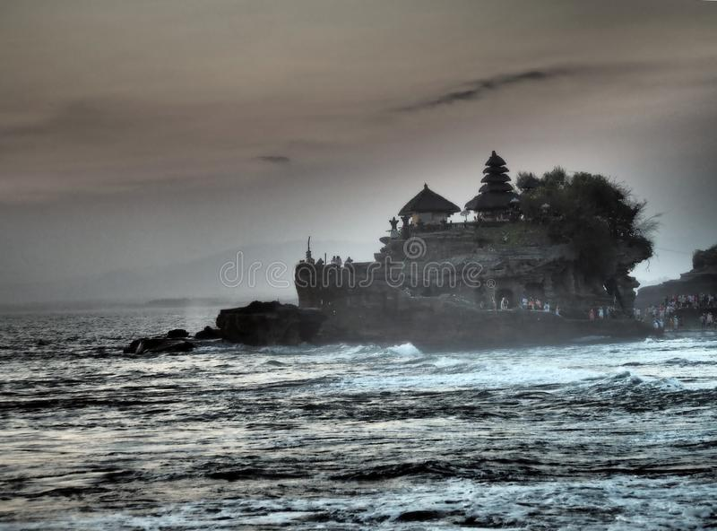 The famous temple Tanah Lot built on a built on a rocky island in the middle of the water at sunset in Bal, Indonesia stock images