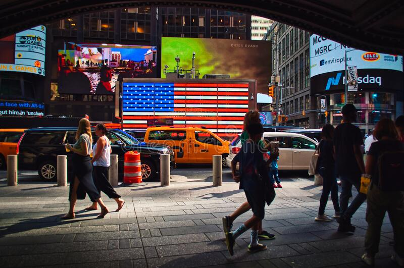 Famous Times Square with big American flag, yellow cab and walking people. stock photo