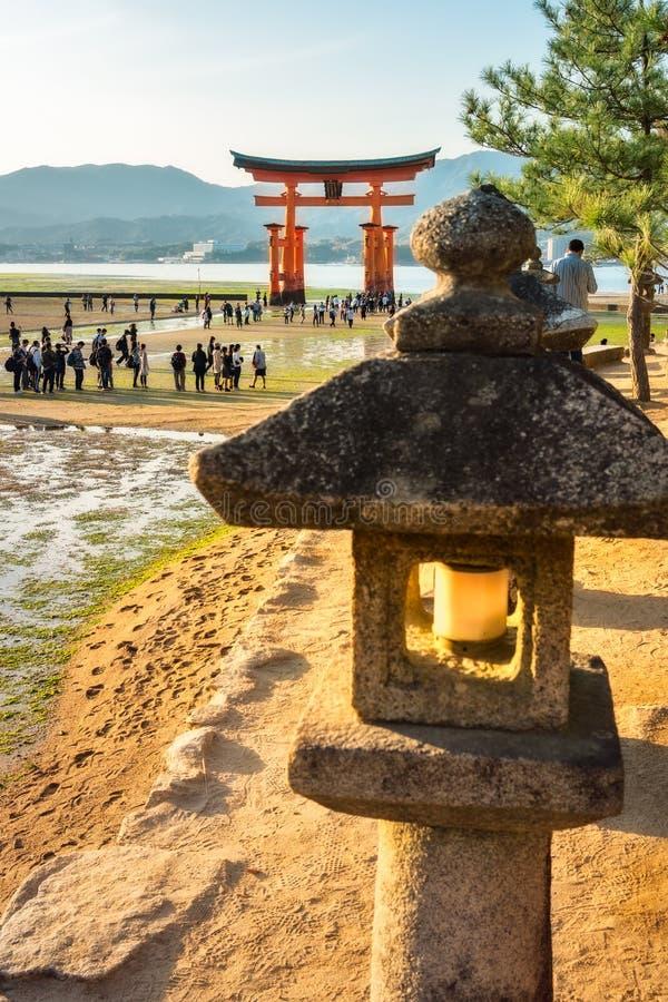 The famous Torii Gate at Miyajima Island, Japan, with a stone lantern in the foreground. Miyajima Island, Hiroshima Prefecture, Japan -November 7, 2018: The stock photo