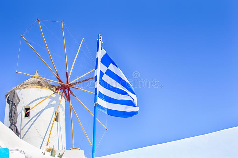 Famous Travel places. Picturesque View of Traditional Windmill with Greek Flag in Oia Village in Santorini Island in Greece stock image