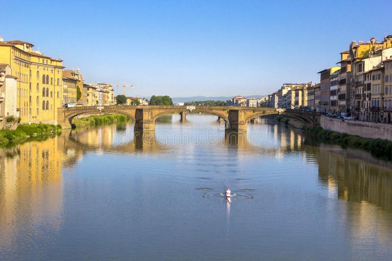 Panoramic view of the Arno River and stone medieval bridge Ponte Vecchio with beautiful reflection of colorful houses, small boat stock images