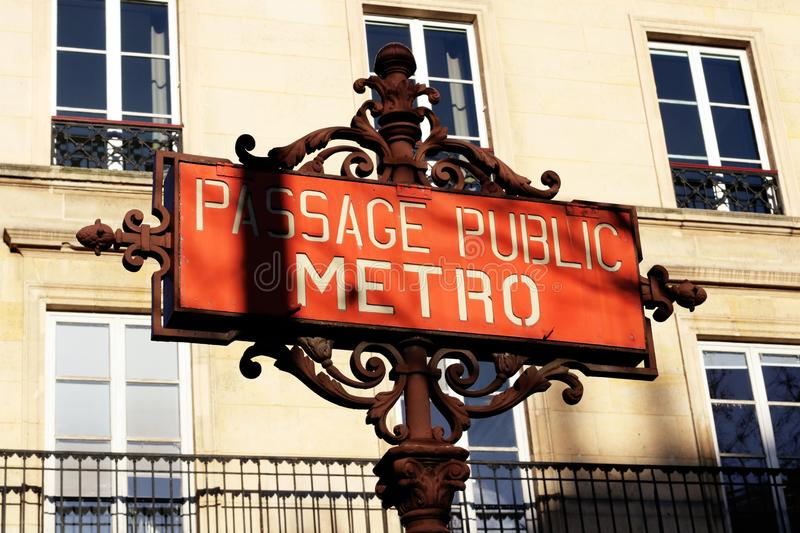 Paris Metro sign with parisian facade in background France. A famous Vintage Art deco style Paris Metro sign with a rare writing public transit passage public royalty free stock images