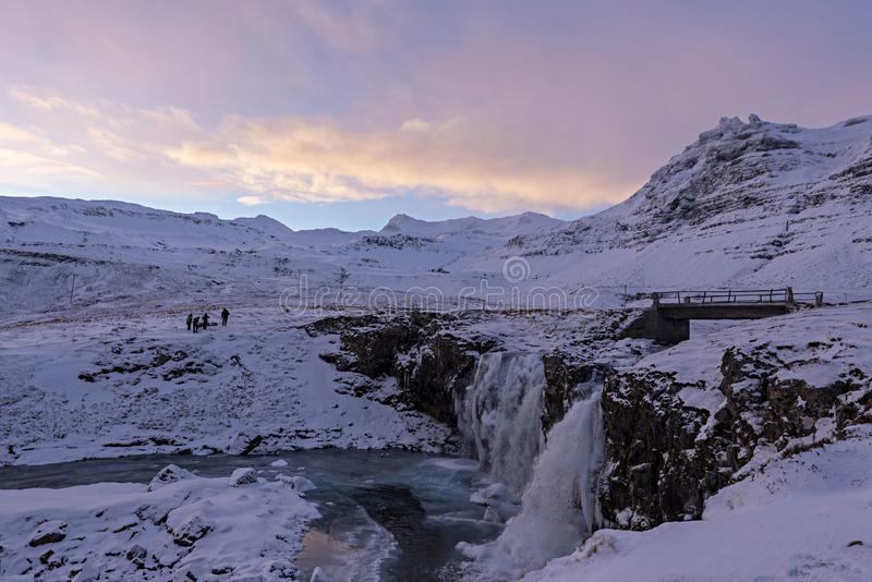 Famous waterfall between the frozen rocky shores of snow mountains and cloudy sky in Iceland. stock images