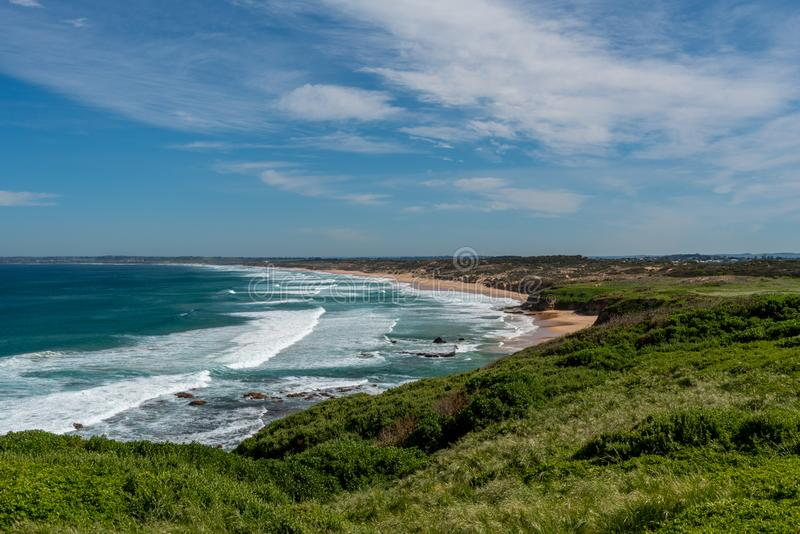 Woolamai Surf Beach. The famous Woolamai Surf Beach on Phillip Island in Victoria Australia, on a partially cloudy day with the waves coming onto the green and royalty free stock photo