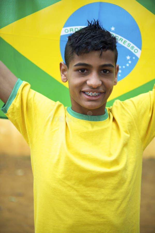 Fanático del fútbol brasileño joven patriótico orgulloso que sostiene la bandera brasileña imagenes de archivo
