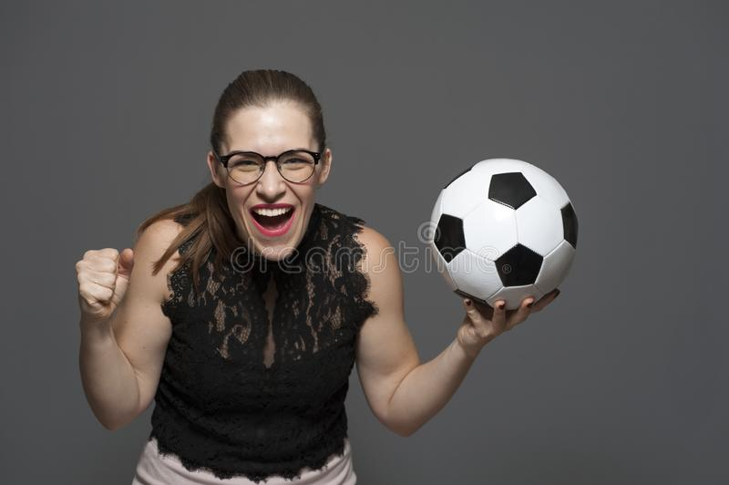 Fan?tico del f?tbol emocionado joven de la mujer que sostiene el bal?n de f?tbol en manos foto de archivo