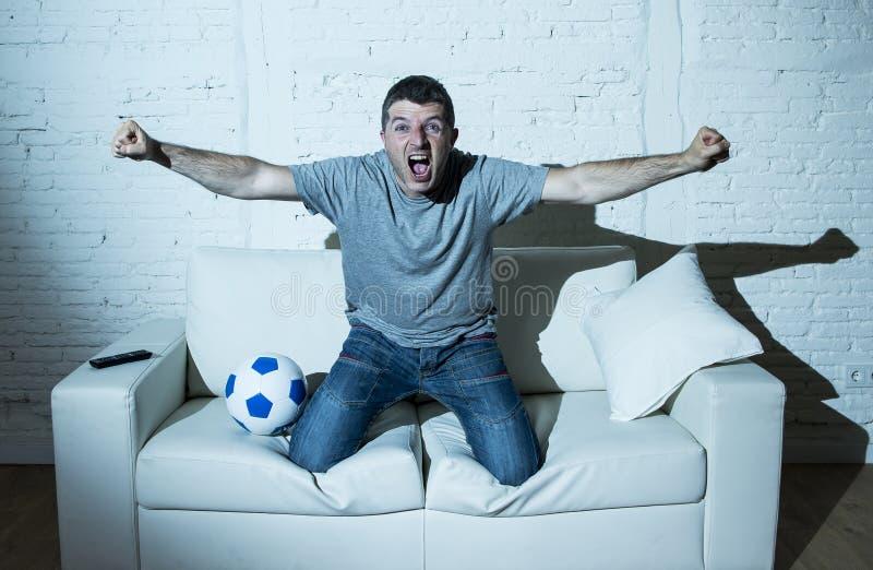 Fanático del fútbol loco que mira el partido de fútbol de la TV solamente el gritar de meta de celebración feliz fotografía de archivo libre de regalías