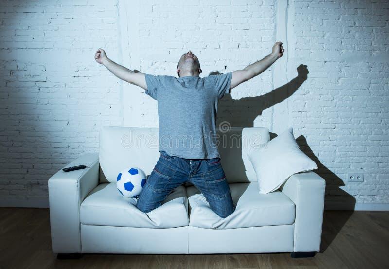 Fanático del fútbol loco que mira el partido de fútbol de la TV solamente el gritar de meta de celebración feliz fotografía de archivo