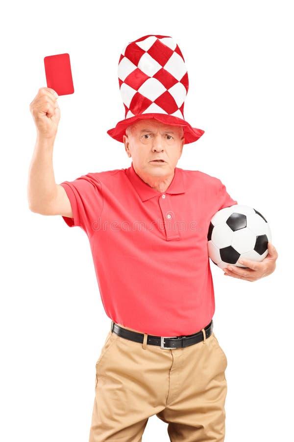 Fanático del fútbol maduro enojado con la bola que da una tarjeta roja fotos de archivo