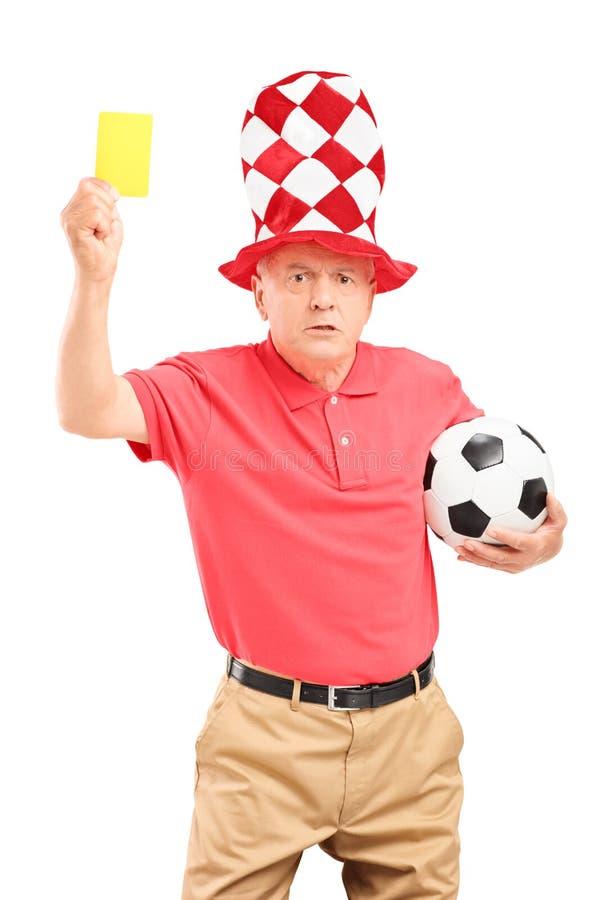 Fanático del fútbol maduro enojado que sostiene una tarjeta amarilla y un balón de fútbol imágenes de archivo libres de regalías