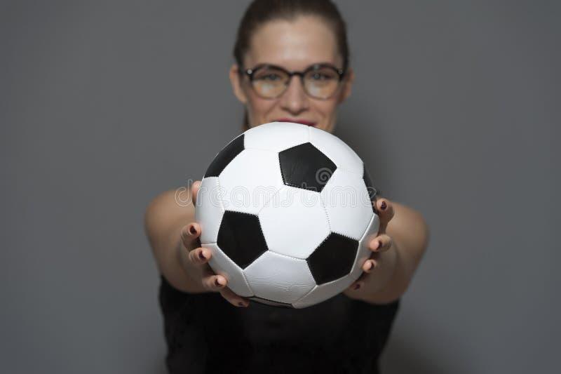 Fan?tico del f?tbol o jugador encantador joven de la mujer que celebra el bal?n de f?tbol en manos fotografía de archivo libre de regalías