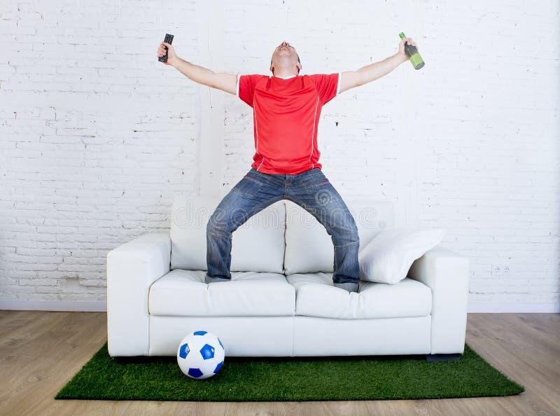 Fanático del fútbol que mira fútbol de la TV el celebrar de meta en sofá en la alfombra de la hierba que emula a la echada del es imagen de archivo