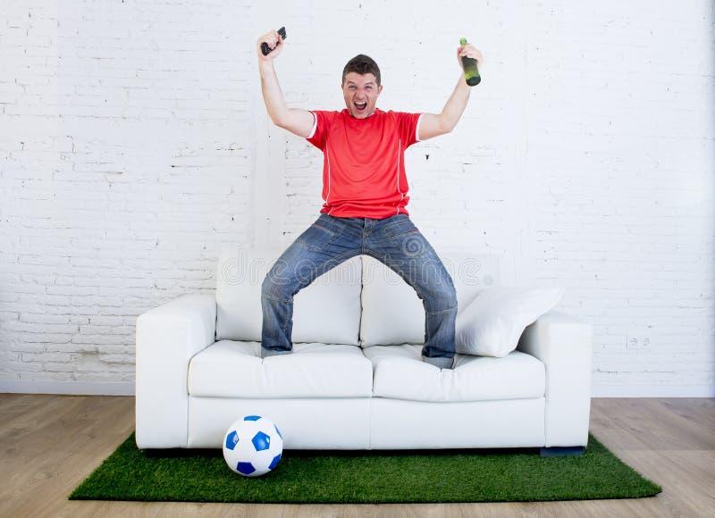 Fanático del fútbol que mira fútbol de la TV el celebrar de meta en sofá en la alfombra de la hierba que emula a la echada del es fotografía de archivo