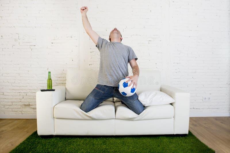 Fanático del fútbol que ve la TV hacer juego en el sofá con la alfombra c de la echada de la hierba fotos de archivo