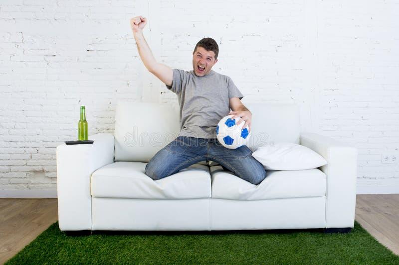Fanático del fútbol que ve la TV hacer juego en el sofá con la alfombra c de la echada de la hierba imagen de archivo libre de regalías