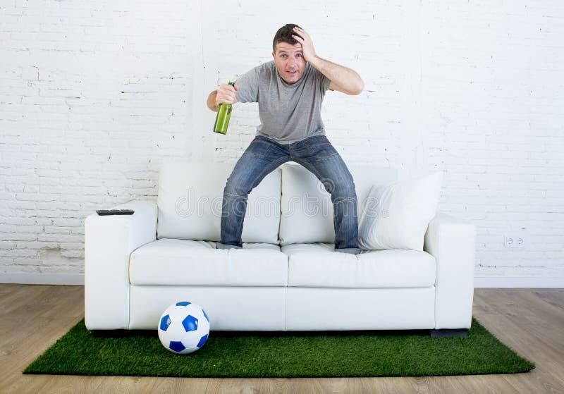 Fanático del fútbol que ve la TV hacer juego en el sofá con la alfombra de la echada de la hierba en la tensión fotos de archivo