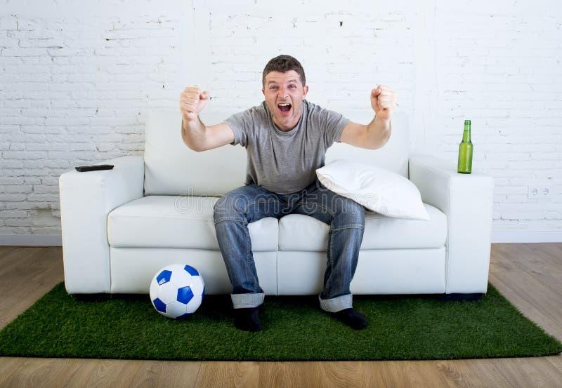 Fanático del fútbol que ve la TV hacer juego en el sofá con la alfombra de la echada de la hierba que celebra meta imagen de archivo