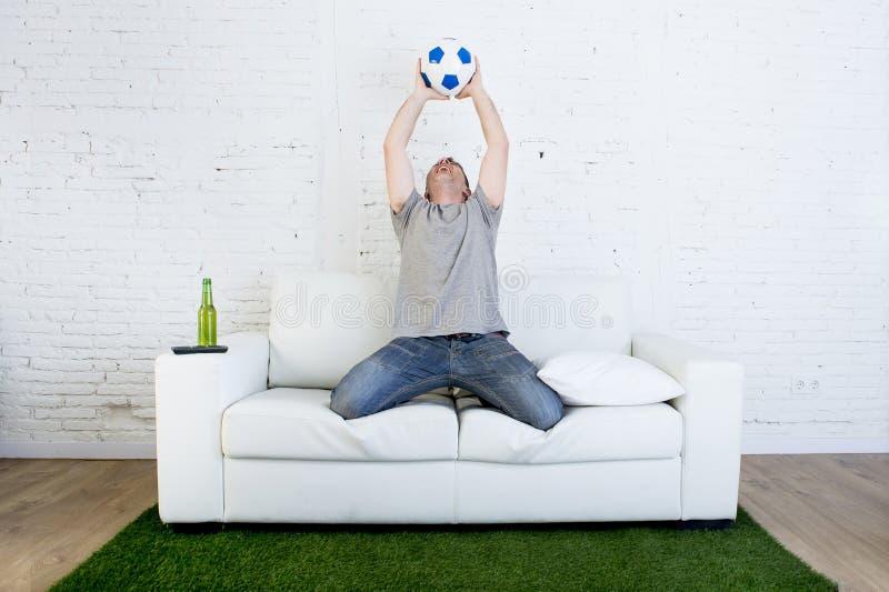 Fanático del fútbol que ve la TV hacer juego en el sofá con la alfombra de la echada de la hierba que celebra meta fotos de archivo libres de regalías