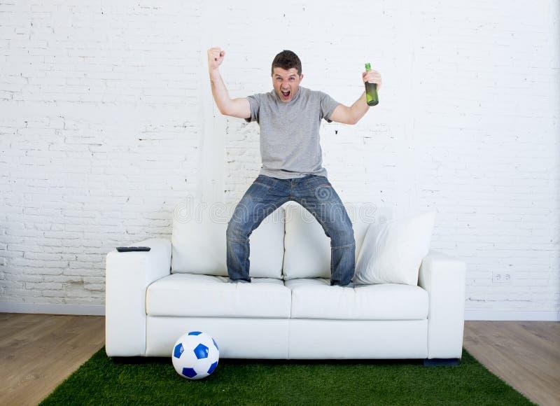 Fanático del fútbol que ve la TV hacer juego en el sofá con la alfombra de la echada de la hierba que celebra meta foto de archivo libre de regalías