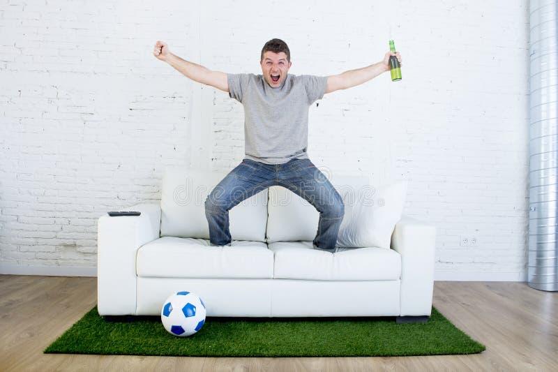 Fanático del fútbol que ve la TV hacer juego en el sofá con la alfombra de la echada de la hierba que celebra meta imágenes de archivo libres de regalías