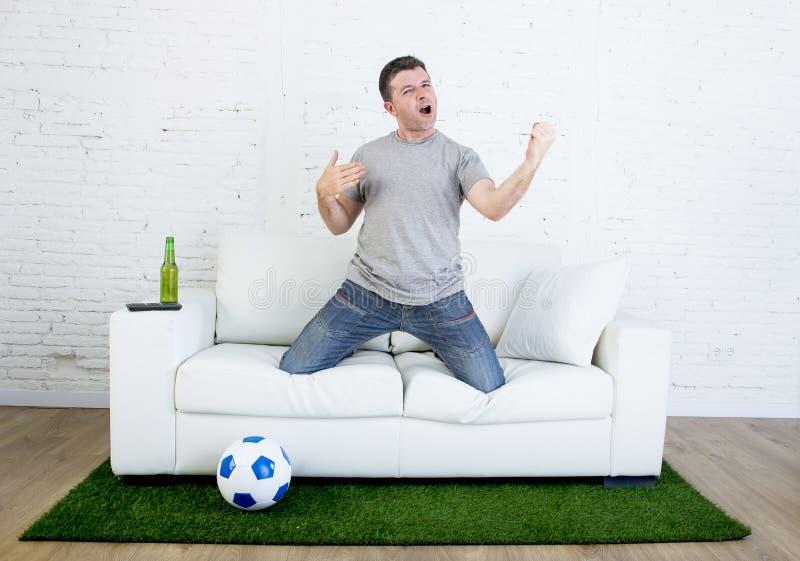 Fanático del fútbol que ve la TV hacer juego en el sofá con la alfombra de la echada de la hierba que celebra meta fotografía de archivo libre de regalías