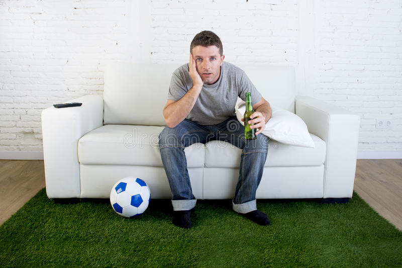 Fanático del fútbol que ve la TV hacer juego en el sofá con la alfombra i de la echada de la hierba imágenes de archivo libres de regalías