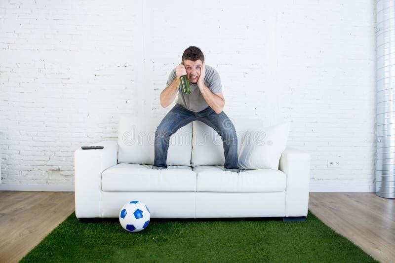 Fanático del fútbol que ve la TV hacer juego en el sofá con la alfombra i de la echada de la hierba foto de archivo