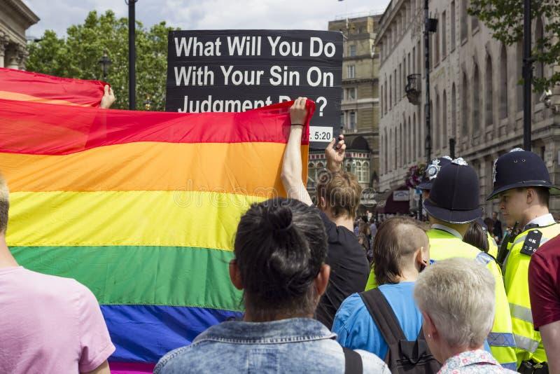 Fanático religioso cubierto por la bandera del arco iris fotografía de archivo libre de regalías