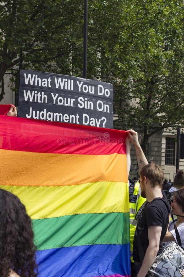 Fanático religioso cubierto por la bandera del arco iris imagen de archivo