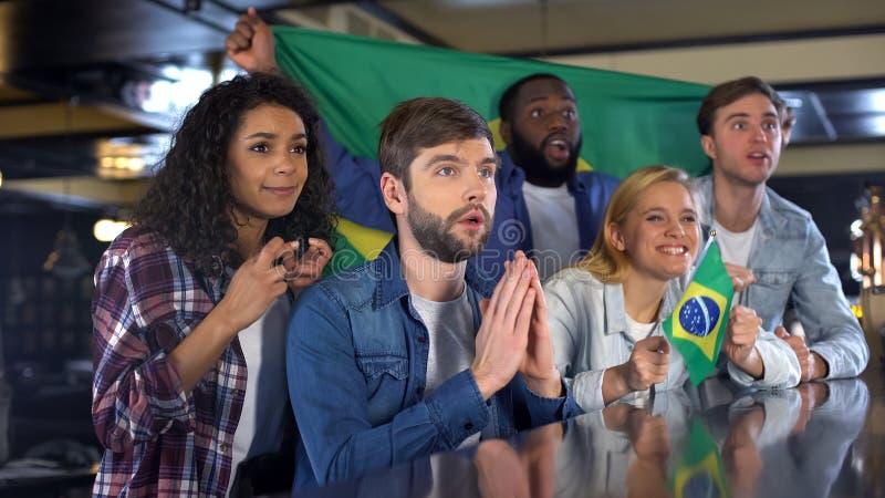 Fanáticos del fútbol ansiosos con las banderas brasileñas que apoyan al equipo nacional en juego foto de archivo libre de regalías