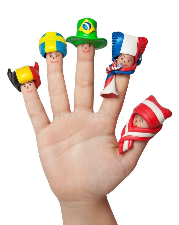 Fanáticos del fútbol de los hombres en casquillos de una arcilla en los fingeres de las manos del ` un s del niño imagen de archivo libre de regalías
