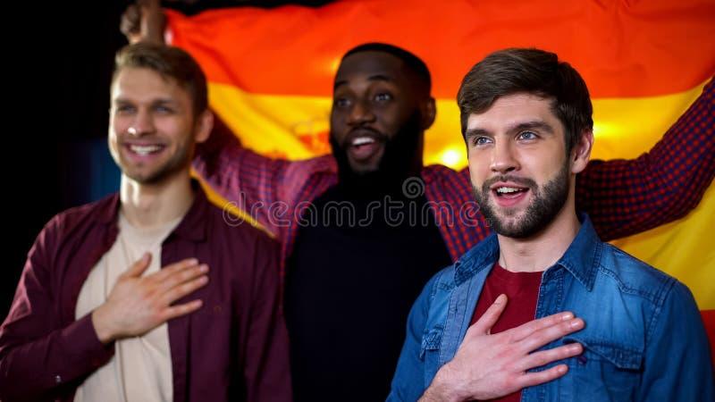 Fanáticos del fútbol masculinos multiétnicos españoles que cantan himno nacional y que agitan la bandera foto de archivo libre de regalías