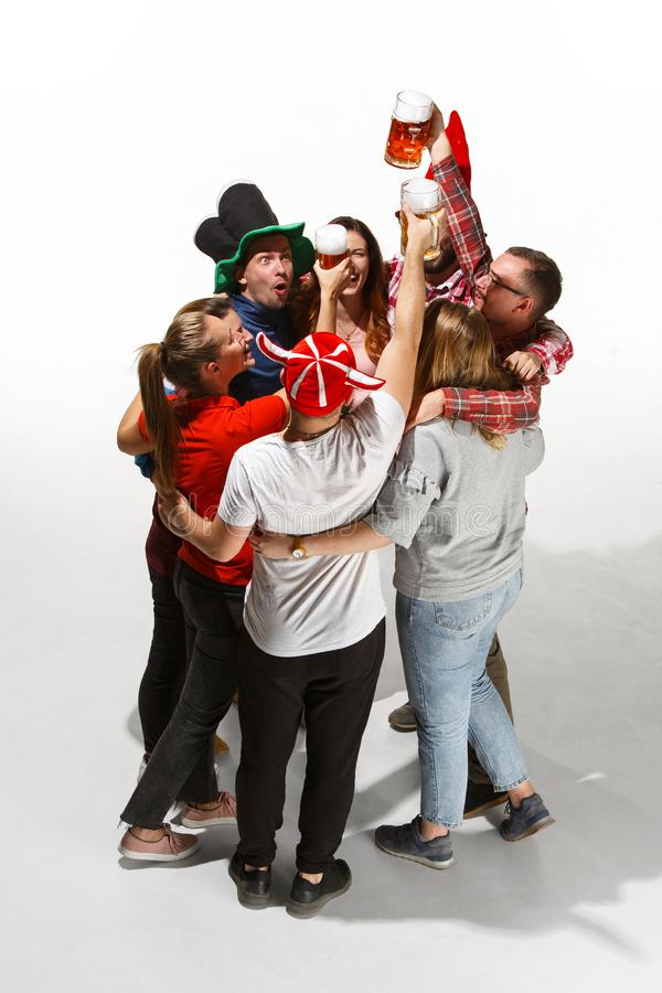 Fanáticos del fútbol que abrazan con las cervezas en el fondo blanco foto de archivo libre de regalías