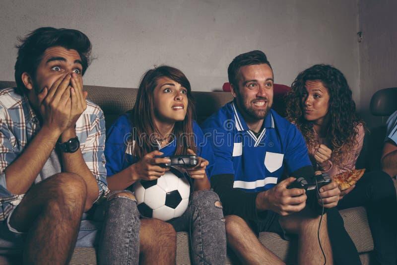 Fanáticos del fútbol que juegan a un videojuego del fútbol fotografía de archivo