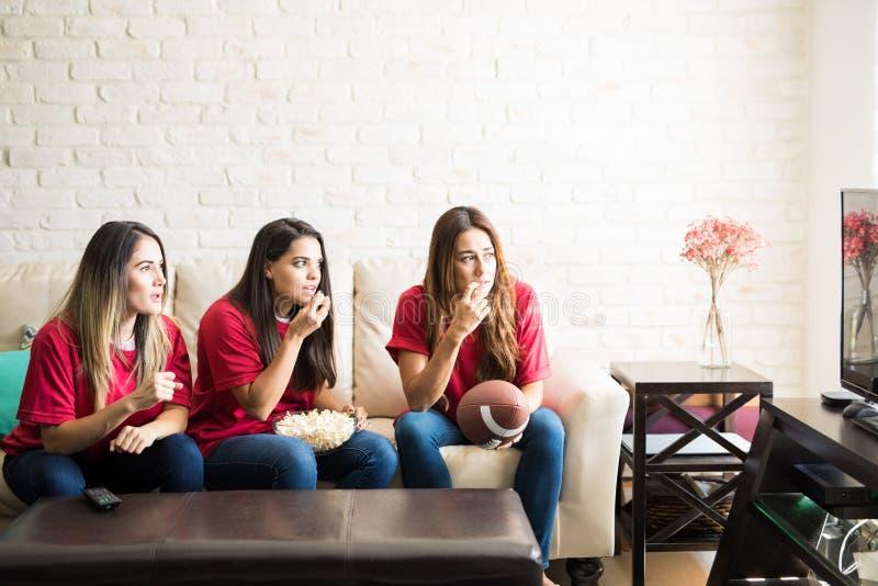 Fanáticos del fútbol que miran un juego en la TV imagen de archivo