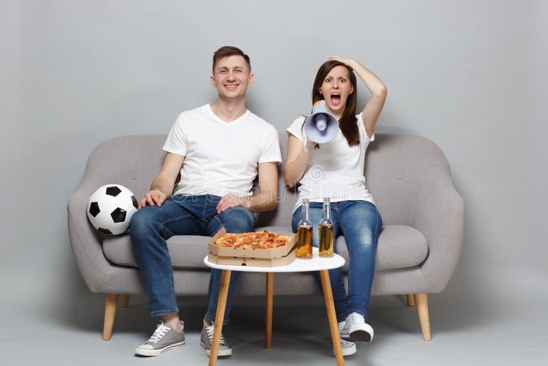 Fanáticos del fútbol sonrientes del hombre de la mujer de los pares Shocked en la alegría blanca de la camiseta encima del grito  imagen de archivo libre de regalías