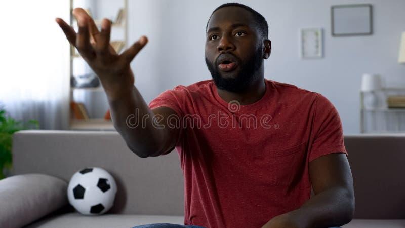 Fan afroamericano che critica gioco dei giocatori, esperto in calcio, cattivo risultato fotografie stock