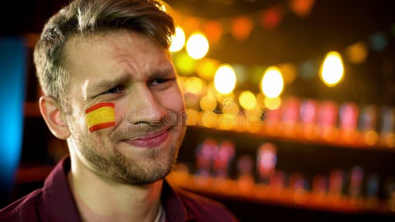 Fan caucásica ansiosa con la bandera española en la mejilla infeliz con resultado del partido imagen de archivo