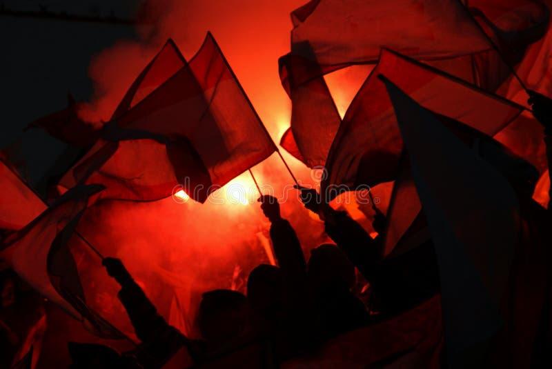 Fan che incoraggiano, gridanti ed ondeggianti le bandiere ad un evento fotografie stock