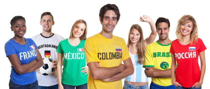 Fan colombien riant avec le groupe encourageant d'autres fans photo stock