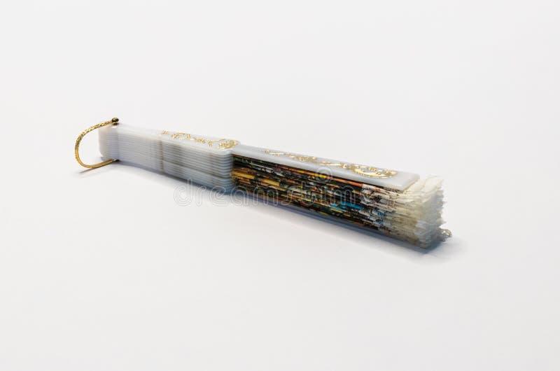 Fan décorative fermée avec un modèle et avec une poignée en plastique blanche d'isolement sur un fond blanc photographie stock libre de droits