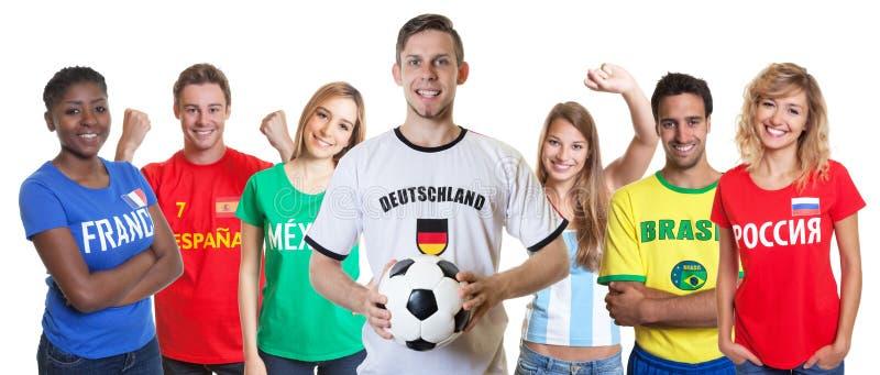 Fan de foot allemand riant avec le groupe encourageant d'autres fans image libre de droits