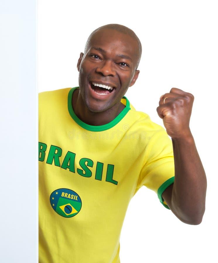 Fan de foot brésilien riant derrière une enseigne photographie stock