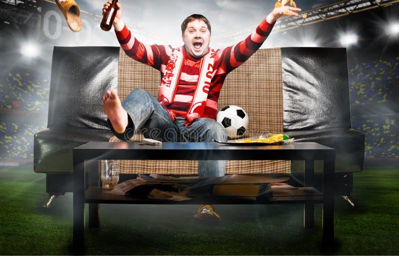 Fan de foot sur le sofa photographie stock