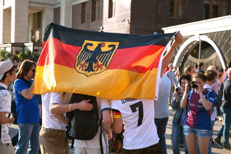 Fan de futebol alemães com a bandeira no quadrado vermelho Campeonato do mundo do futebol fotografia de stock royalty free